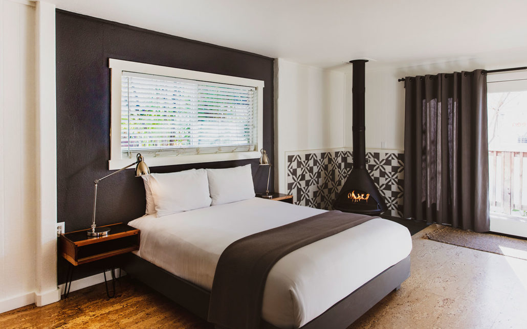boon hotel + spa. room interior. bed with fireplace.